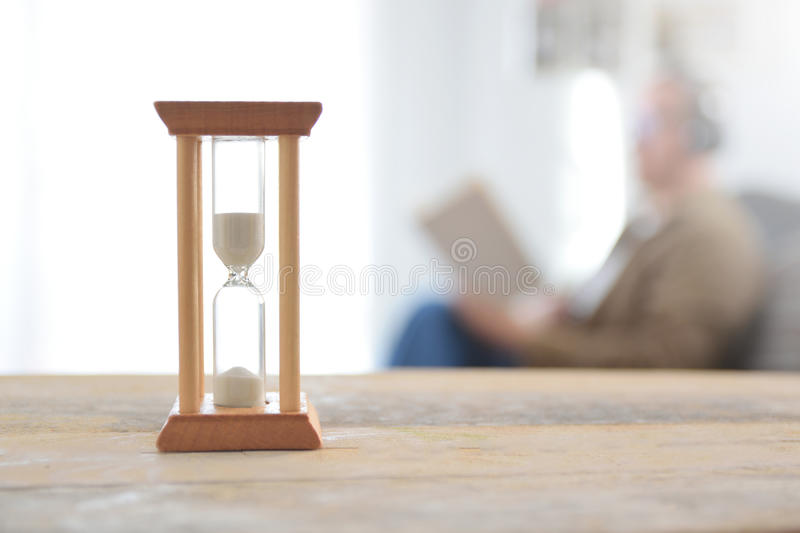 Person having some free time reading a book. An old hourglass on a wooden white table. stock photo