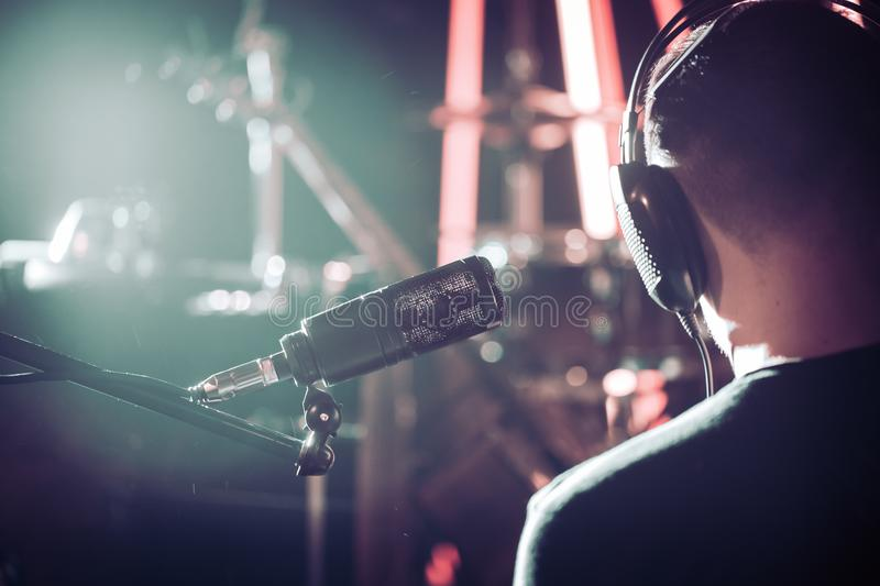 Person with headphones and Studio microphone close-up, in a recording Studio or concert hall, with a drum set. stock photos