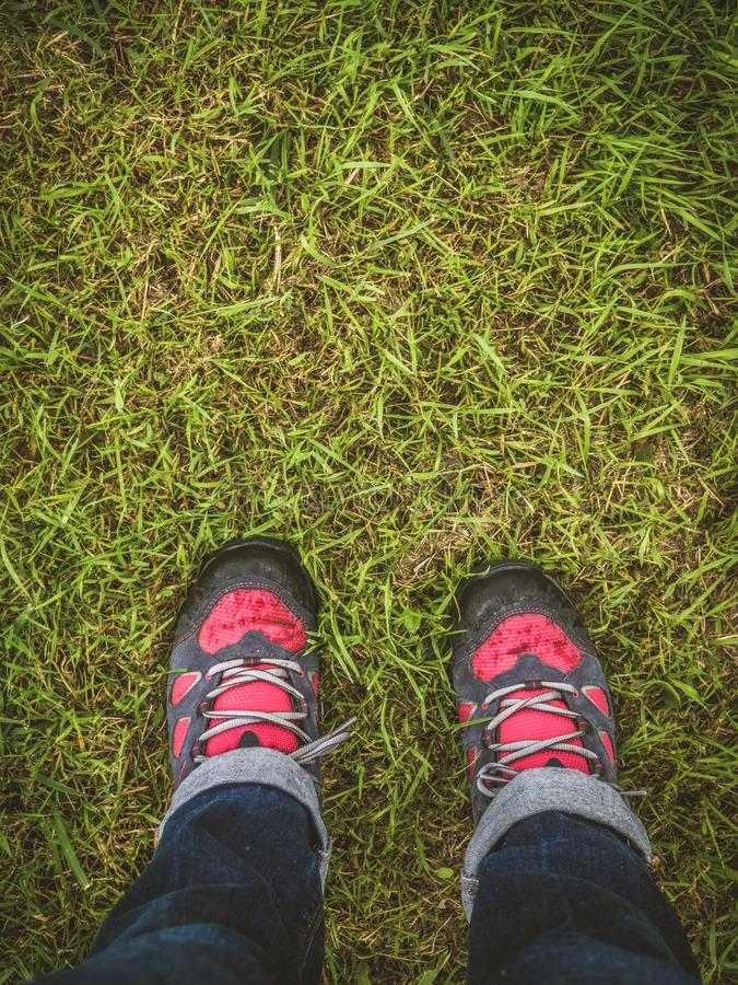 Person with hiking boots on the grass. With copy space stock photo