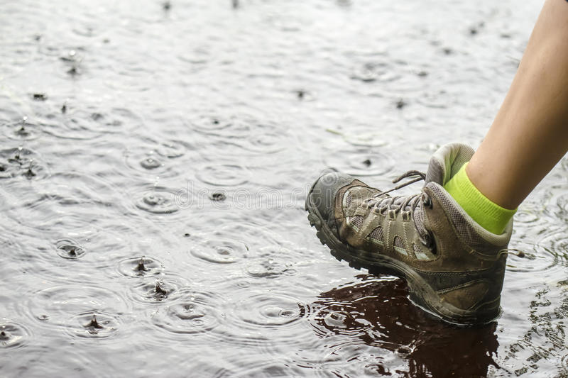 Person in hiking boots walking on water in the rain. Person in tourist waterproof hiking boots walking on water in the puddles in the rain stock photos