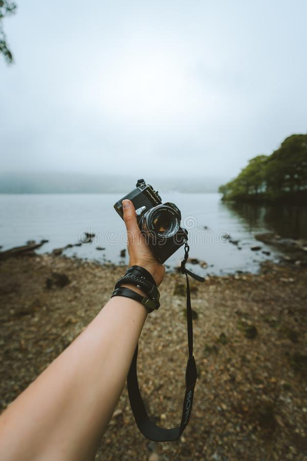 Person Holding Black Camera Front Body of Water royalty free stock photo