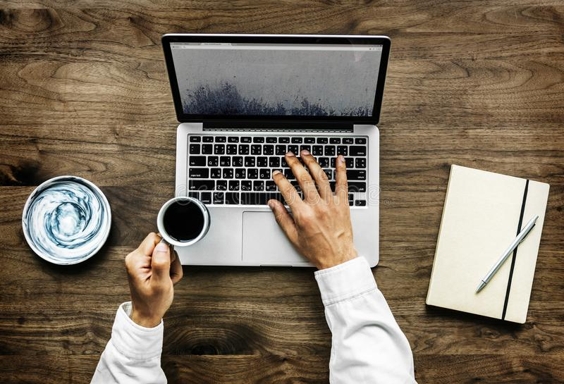 Person Holding Black Ceramic Cup and Macbook Pro royalty free stock photos