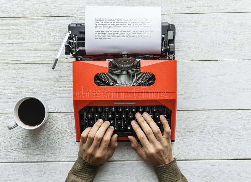 Person Holding Black and Orange Typewriter stock photo