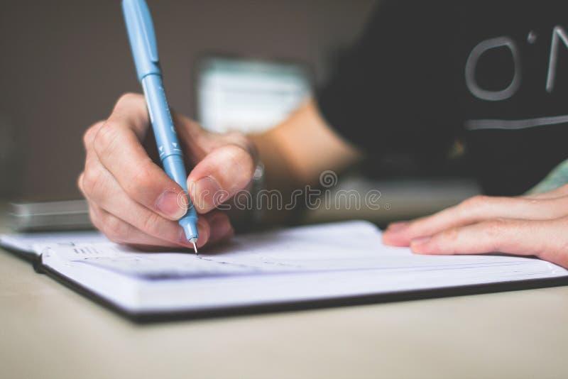 Person Holding Blue Ballpoint Pen-Schreiben im Notizbuch stockfoto