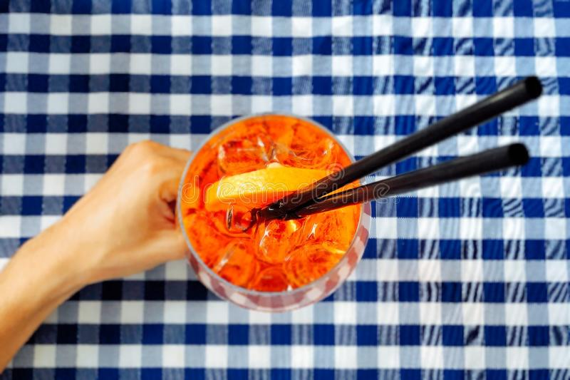 Person Holding Clear Drinking Glass With Two Black Straws royalty free stock images