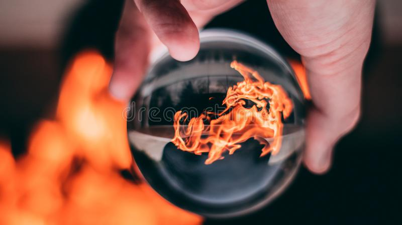 Person Holding Clear Glass Ball With Flame stock images