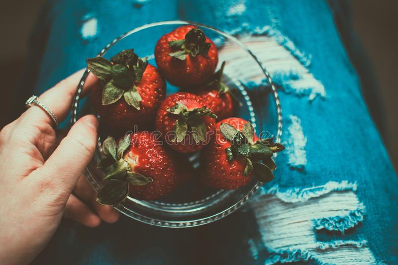 Person Holding Clear Glass Bowl of Strawberries royalty free stock photography