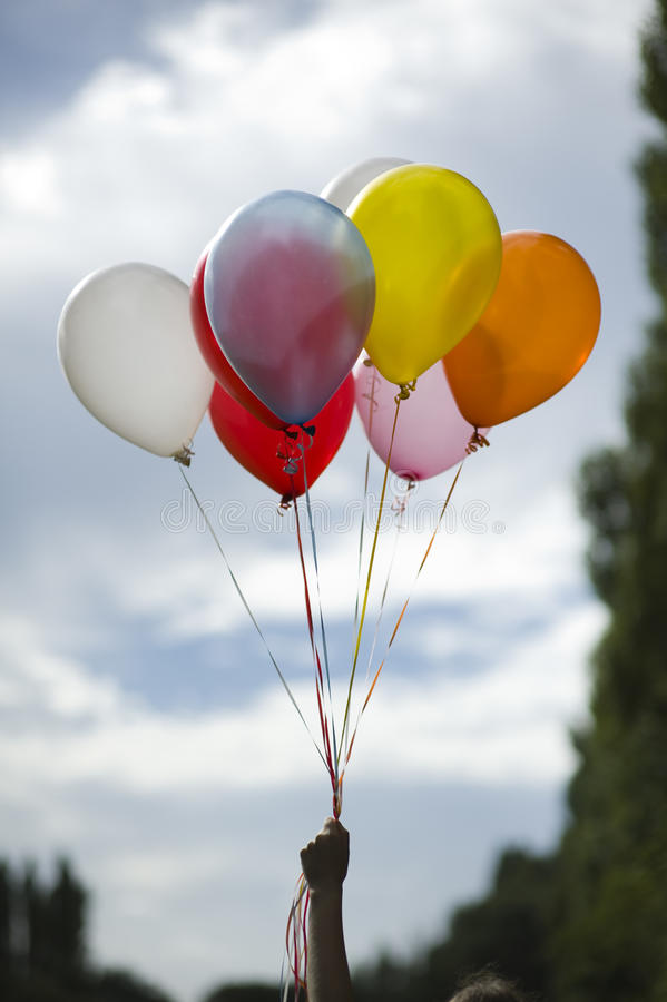 Person holding colored helium balloons. Person holding multi colored helium ballons royalty free stock image