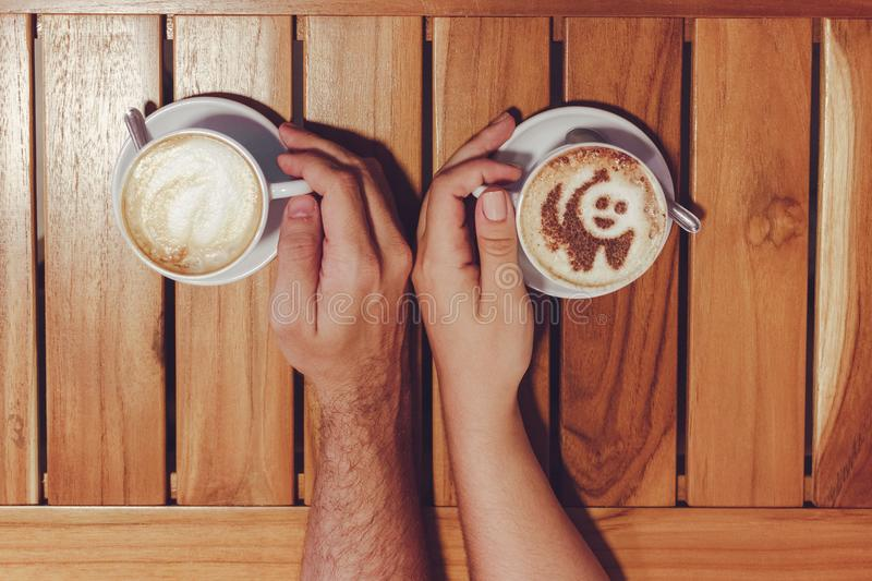 Person Holding Cup of Coffees on Table stock image