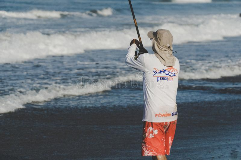 Person Holding Fishing Rod on Beach stock photography
