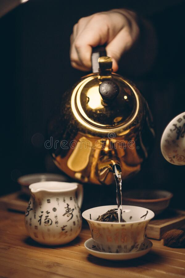 Person Holding Gold Teapot Pouring White Ceramic Teacup royalty free stock photos