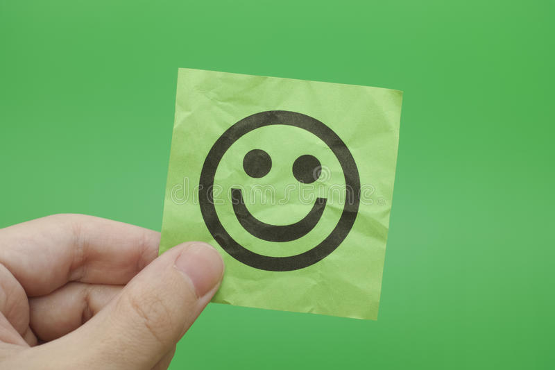 Person holding green paper note with Happy Face. In his hand. Green background royalty free stock photography