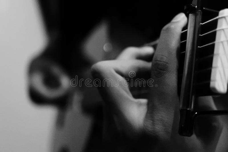 Person Holding Guitar in Grayscale Photography royalty free stock photo