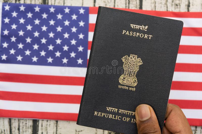 Person holding Indian Passport with hand on a US or american flag as background. stock photos