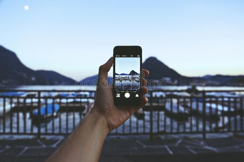 Person Holding Iphone Taking Picture of Mountain Near Body of Water stock photos