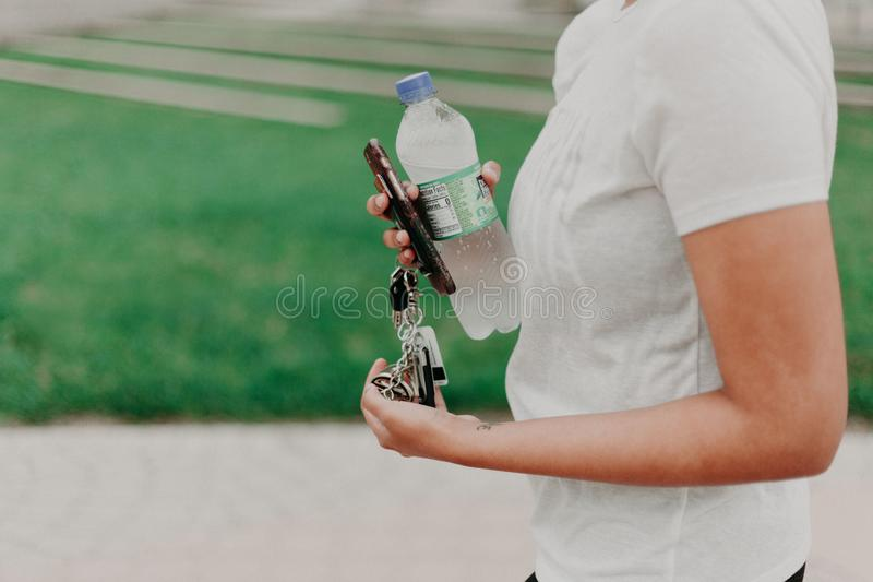Person Holding Key, Smartphone, And Plastic Bottle stock photos