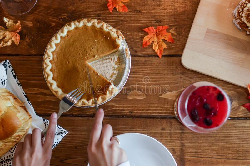 Person Holding Knife and Fork Cutting Slice of Pie on Brown Wooden Table royalty free stock images
