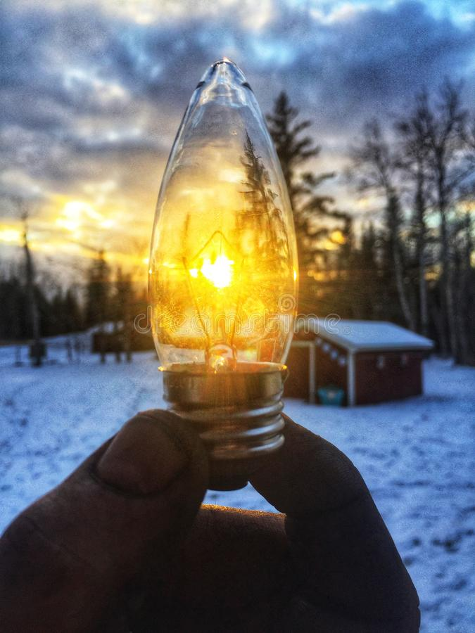 Person Holding Led Bulb in Front of Sunrise Photo royalty free stock images