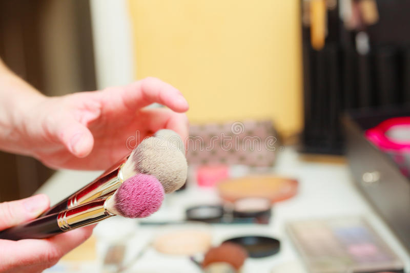 Person holding makeup brushes for blush and powder royalty free stock image