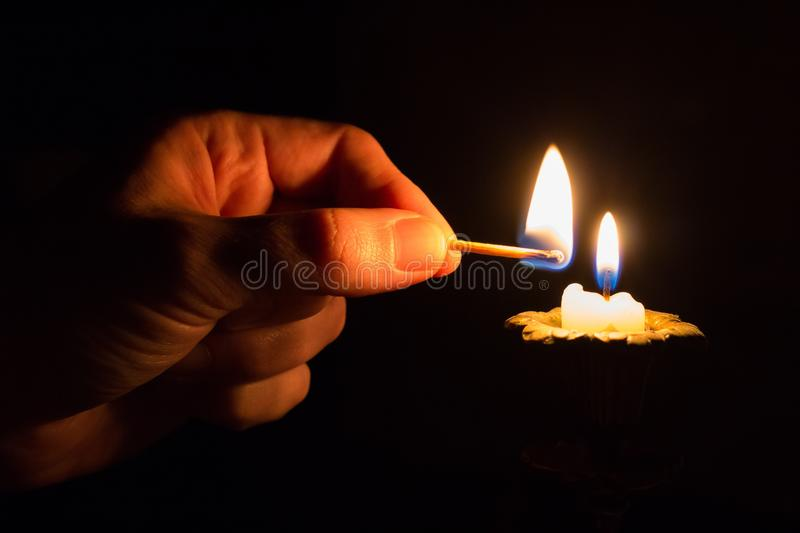 Person Holding Match Stick With Fire in Front of Candle With Fire royalty free stock images