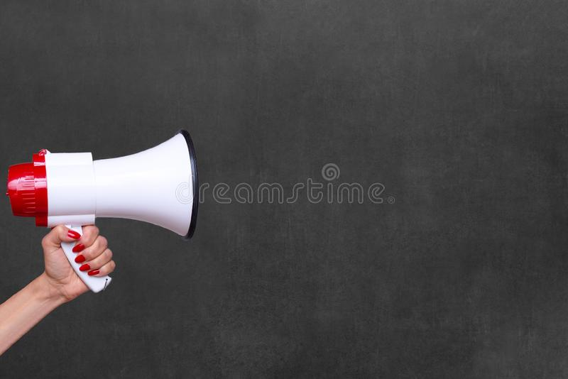 Person holding a megaphone or loud hailer. Person holding a megaphone, bullhorn or loud hailer to the side over a blank chalkboard with copy space royalty free stock photography