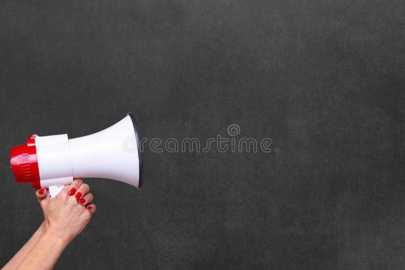 Person holding a megaphone or loud hailer. Person holding a megaphone, bullhorn or loud hailer to the side over a blank chalkboard with copy space stock photo