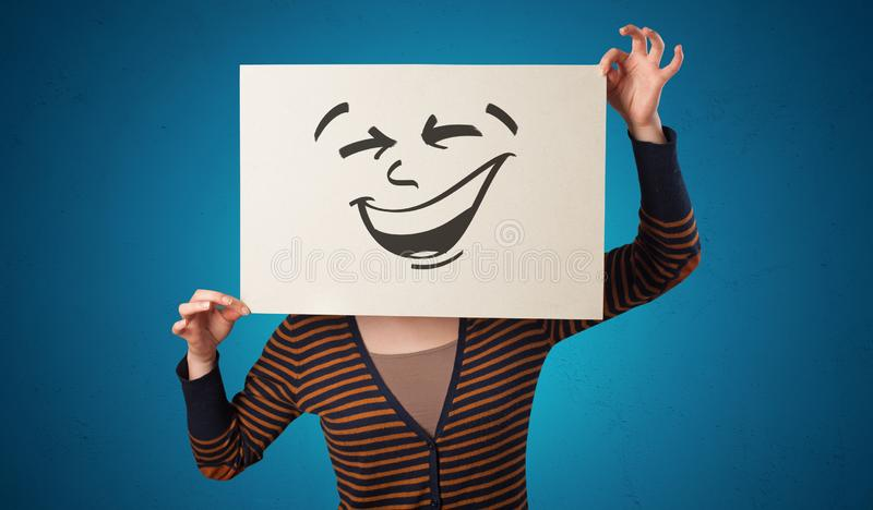 Person holding a paper with cool emoticon face. Casual person holding a paper with cool emoticon in front of his facen royalty free stock photos