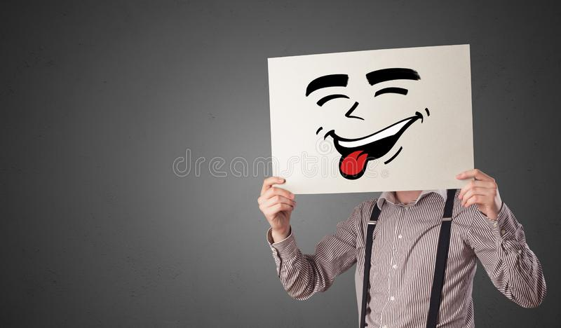 Person holding a paper with cool emoticon face. Casual person holding a paper with cool emoticon in front of his facen royalty free stock image