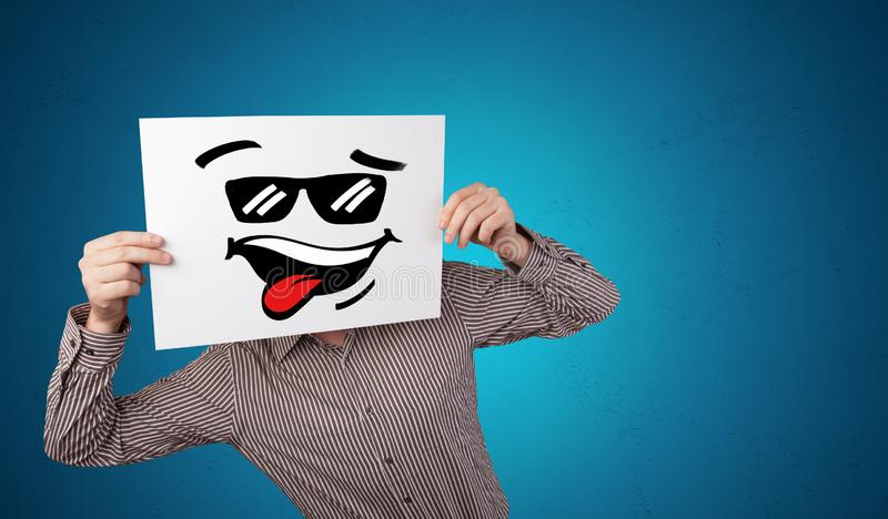 Person holding a paper with cool emoticon face. Casual person holding a paper with cool emoticon in front of his facen royalty free stock images