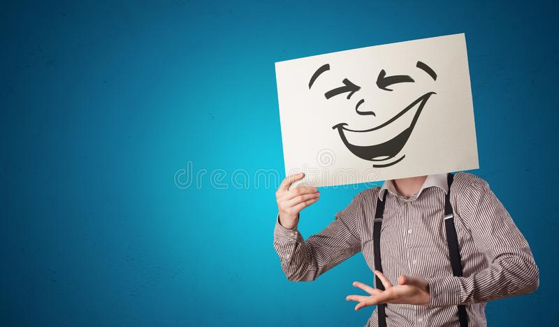 Person holding a paper with cool emoticon face. Casual person holding a paper with cool emoticon in front of his face royalty free stock photography