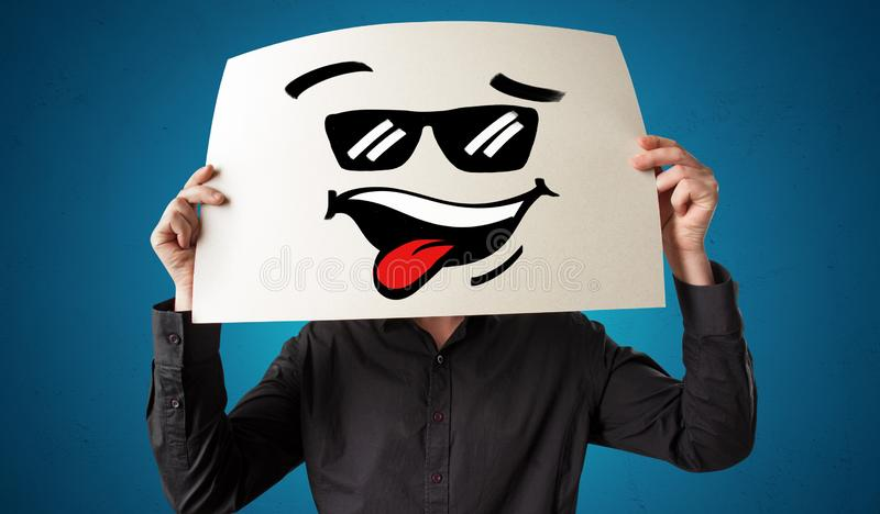 Person holding a paper with cool emoticon face. Casual person holding a paper with cool emoticon in front of his facen stock images