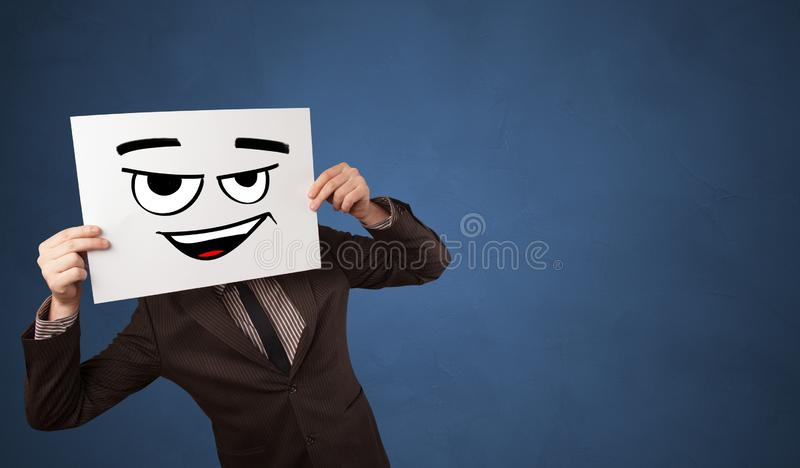Person holding a paper in front of his face with doodle emoticon. Casual person holding a paper in front of his face with drawn emoticon face n royalty free stock images