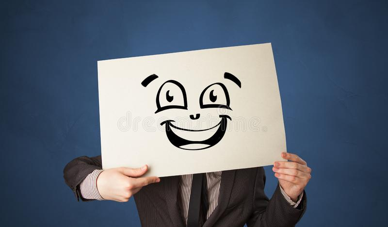 Person holding a paper in front of his face with doodle emoticon. Casual person holding a paper in front of his face with drawn emoticon face n royalty free stock photos