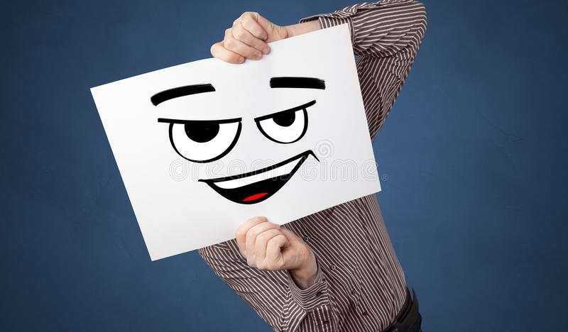 Person holding a paper in front of his face with doodle emoticon. Casual person holding a paper in front of his face with drawn emoticon face n royalty free stock photography