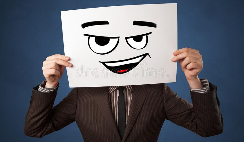 Person holding a paper in front of his face with doodle emoticon. Casual person holding a paper in front of his face with drawn emoticon face n royalty free stock photo