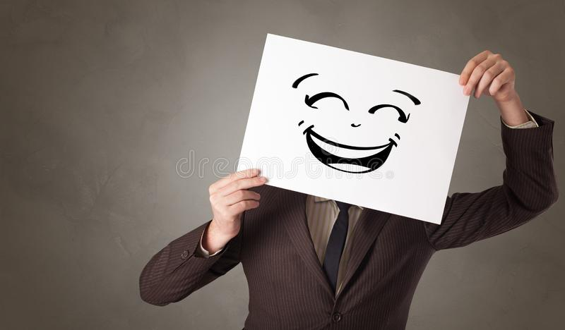 Person holding a paper in front of his face with doodle emoticon. Casual person holding a paper in front of his face with drawn emoticon face royalty free stock photo