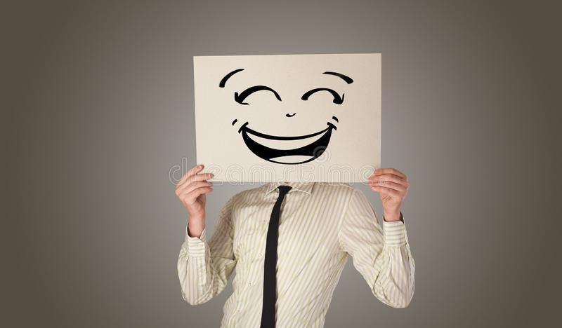 Person holding a paper in front of his face with doodle emoticon. Casual person holding a paper in front of his face with drawn emoticon face n stock photos