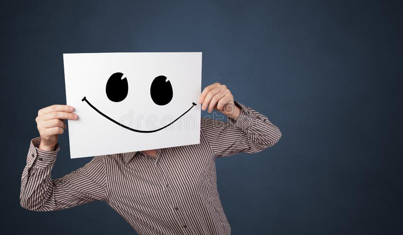 Person holding a paper with funny emoticon in front of her face. Casual person holding a paper with funny emoticon in front of her facen stock images