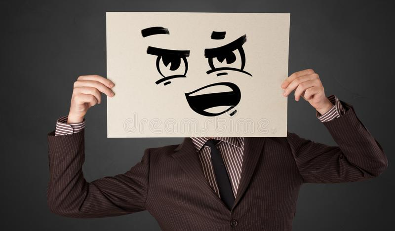 Person holding a paper with funny emoticon in front of her face. Casual person holding a paper with funny emoticon in front of her face stock photography