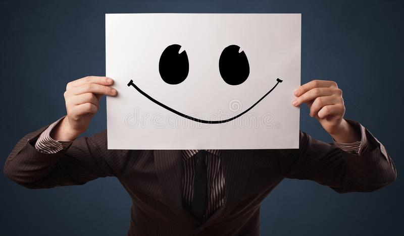 Person holding a paper with funny emoticon in front of her face. Casual person holding a paper with funny emoticon in front of her face royalty free stock photos