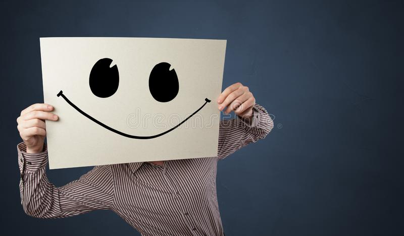 Person holding a paper with funny emoticon in front of her face. Casual person holding a paper with funny emoticon in front of her facen royalty free stock photography