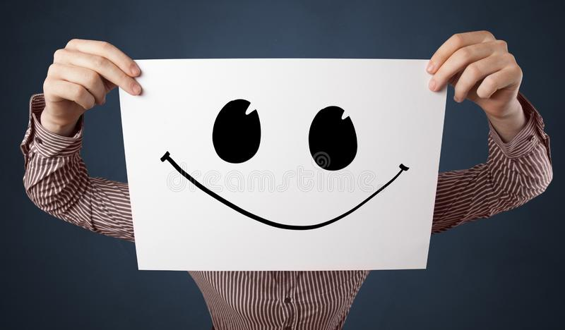 Person holding a paper with funny emoticon in front of her face. Casual person holding a paper with funny emoticon in front of her facen stock image