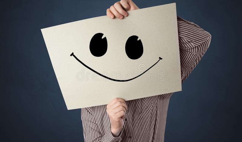 Person holding a paper with funny emoticon in front of her face. Casual person holding a paper with funny emoticon in front of her facen royalty free stock photos