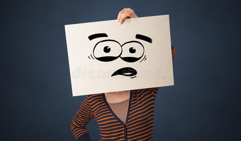 Person holding a paper with funny emoticon in front of her face. Casual person holding a paper with funny emoticon in front of her face royalty free stock photography