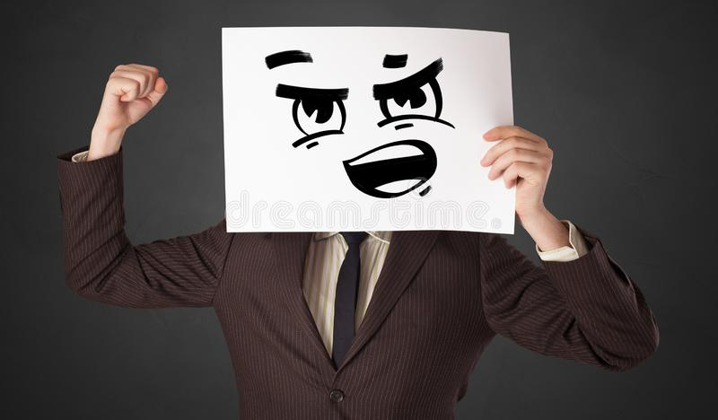 Person holding a paper with funny emoticon in front of her face. Casual person holding a paper with funny emoticon in front of her facen stock photo