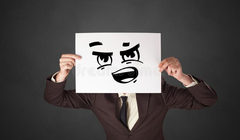 Person holding a paper with funny emoticon in front of her face. Casual person holding a paper with funny emoticon in front of her facen royalty free stock image