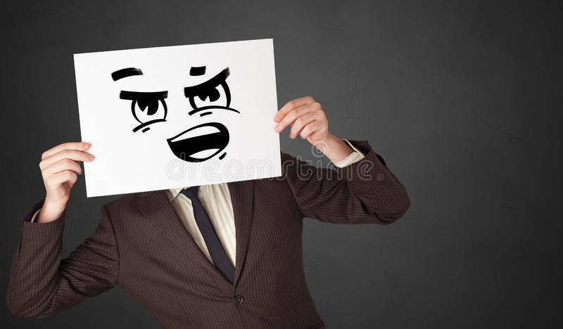 Person holding a paper with funny emoticon in front of her face. Casual person holding a paper with funny emoticon in front of her face royalty free stock photo