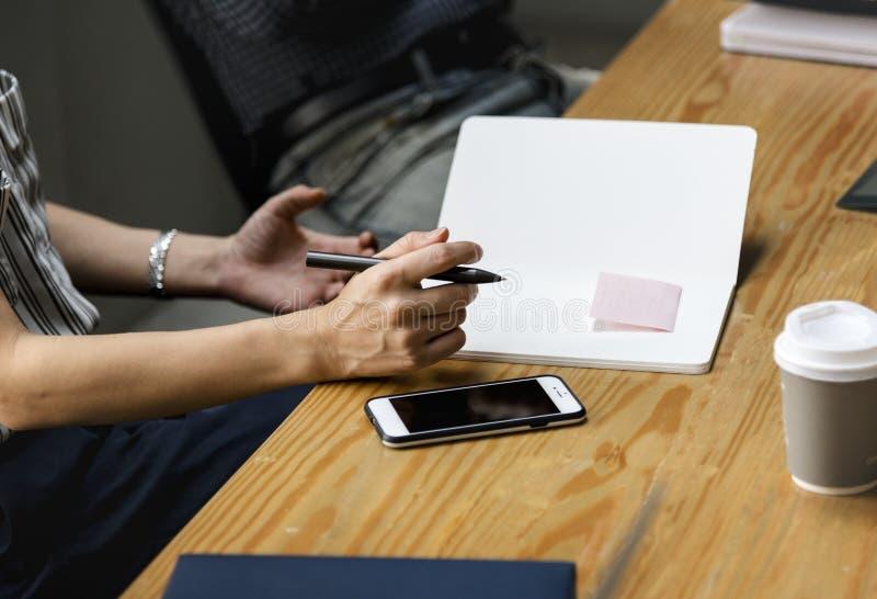 Person Holding Pen und Notebook lizenzfreie stockfotos