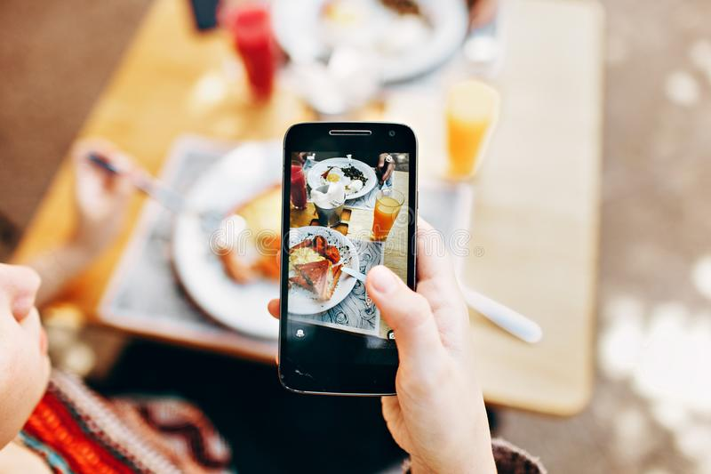 Person Holding Phone Taking Picture of Served Food stock image