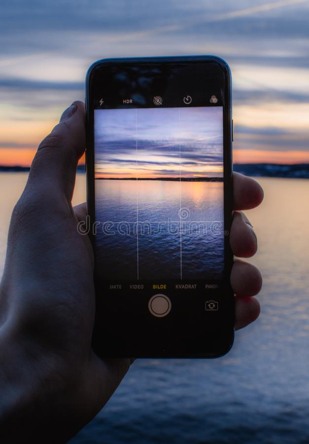 Person Holding Post-2014 Iphone Taking a Photo of Body of Water stock photos